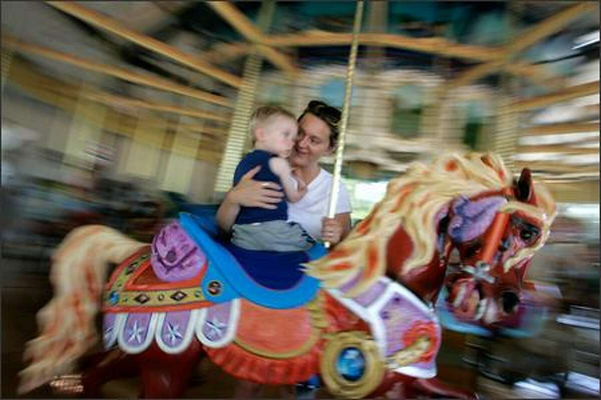 Riders on the historic carousel at Woodland Park Zoo in Seattle on Sunday included Ryan Hundren, 2, and mom Ronda of Renton. The Philadelphia Toboggan Co. built the carousel in 1918 for the Cincinnati Zoo. The carousel was a gift to Woodland Park Zoo from Linda and Tom Allen of the Alleniana Foundation, and it was opened Saturday. The pavilion and restoration cost $3.2 million.