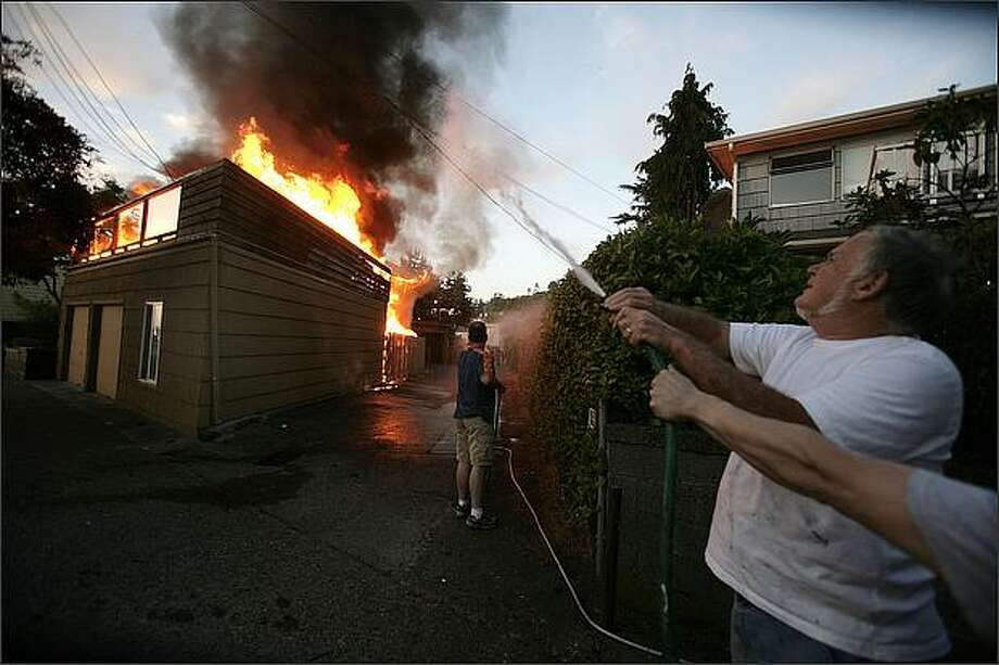 Hudson Burke uses a garden hose to keep the flames at an Alki Beach duplex across from spreading. The fire began about 8:40 Thursday night. Seattle P-I photo/Meryl Schenker