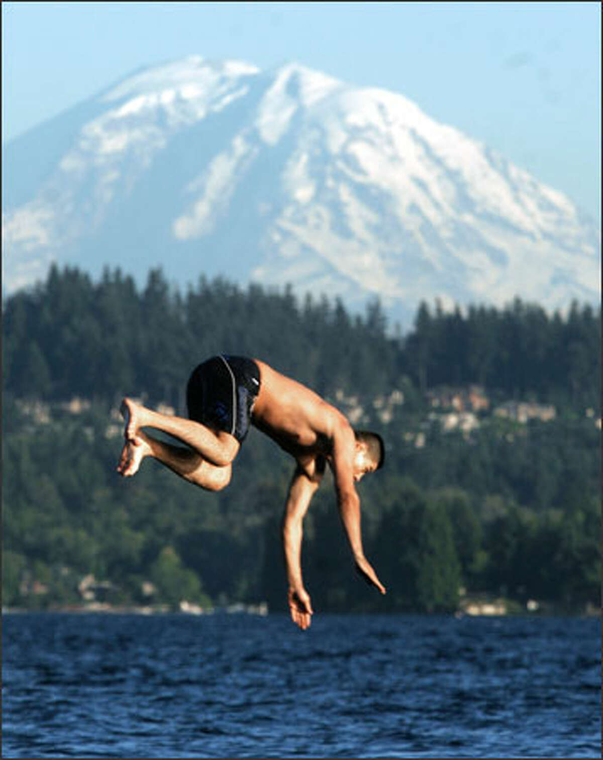 Moises Delgadillo dives off the swimming dock at Warren G. Magnuson Park in Seattle at dusk. Local temperatures hit the 80s this past week.