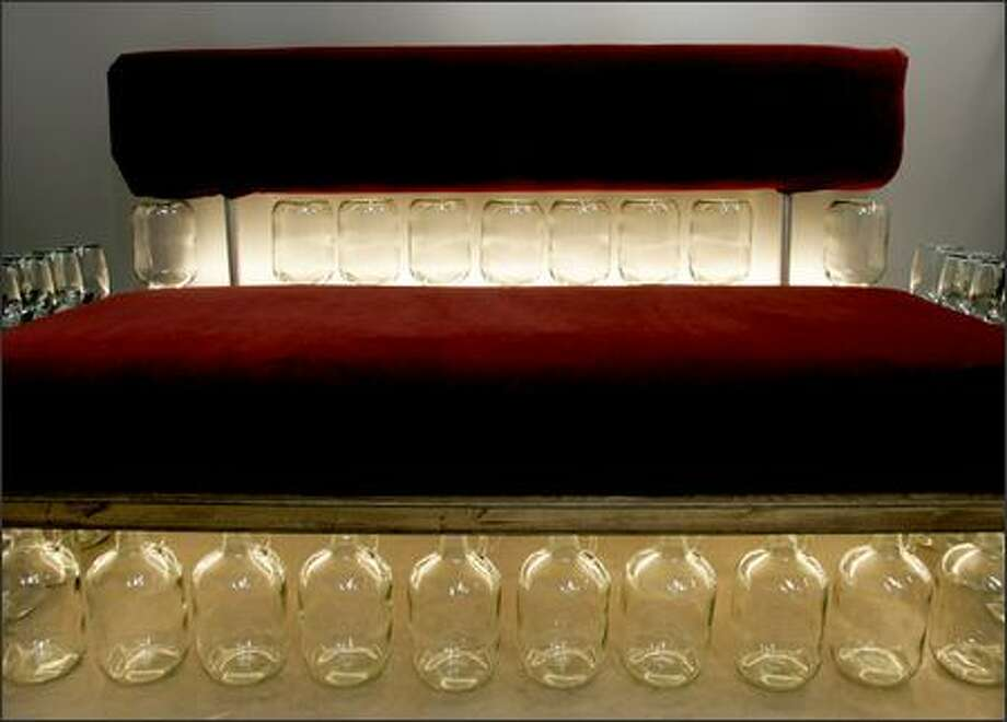 The Cabernet Couch fuses a futon mattress with 49 vino jugs, which serve as the couch's legs, armrests and back while neon lights illuminate the glass.  It was created by the artists at Western Neon. Photo: Mike Kane, Seattle Post-Intelligencer / Seattle Post-Intelligencer