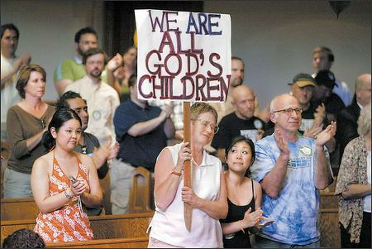 Harriett Cody, with sign, her daughter Halley Cody, second from right, and her husband, Harvey Sadis, all of Seattle, applaud a speaker's vow to continue the fight for gay marriage rights during a community gathering at Seattle First Baptist Church in Seattle on Wednesday, after the state Supreme Court upheld a ban on gay marriage.