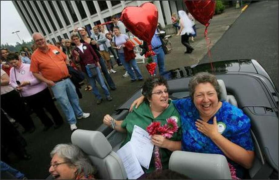 Lisa Brodoff, left, and Lynn Grotsky are all smiles after getting into a convertible to begin their celebration after registering as domestic partners in Olympia, WA on Monday, July 23, 2007. The couple, from Lacey, have been together for 26 years. Photo: Dan DeLong, Seattle Post-Intelligencer / Seattle Post-Intelligencer