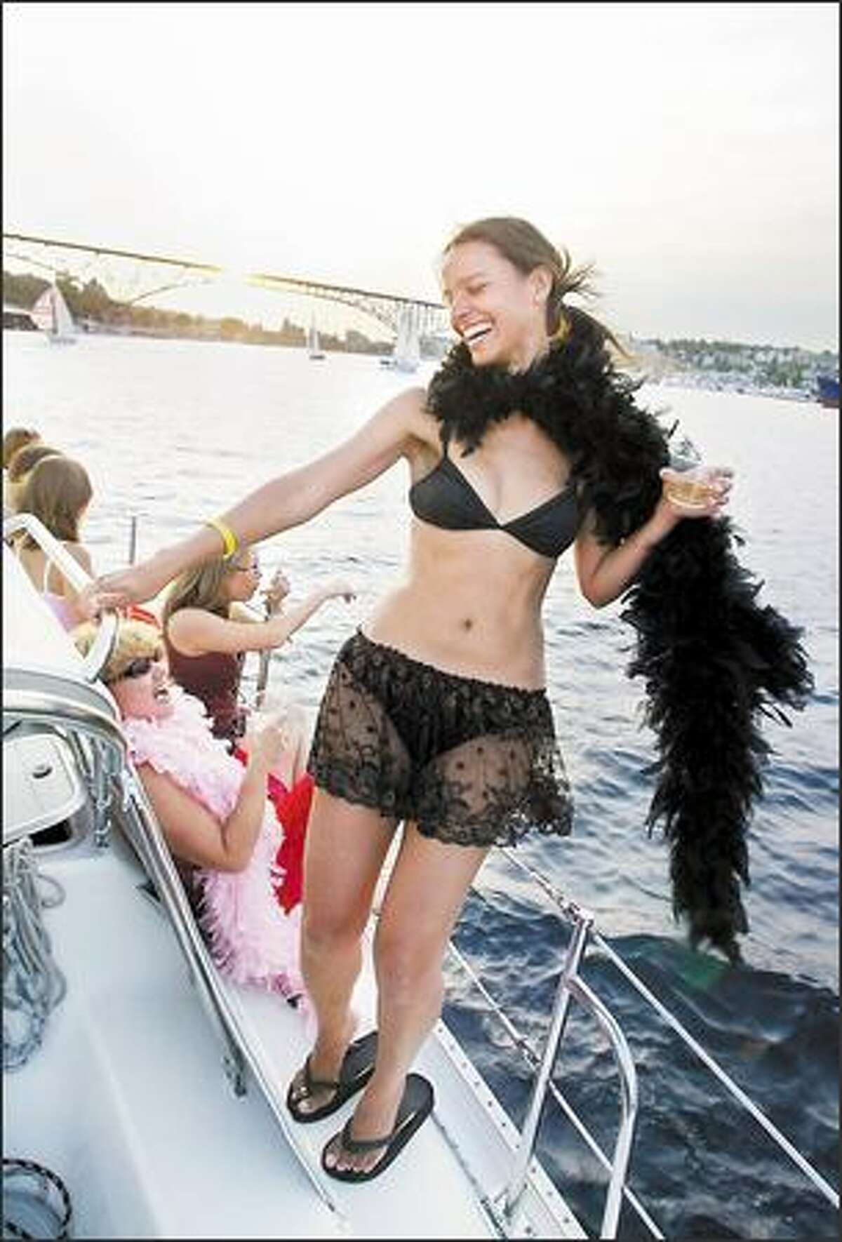 Wanda Layton of Seattle, standing right, and Colleen Galbraith, center, break out their boas to party on the boat Mata Hari in the Duck Dodge race.