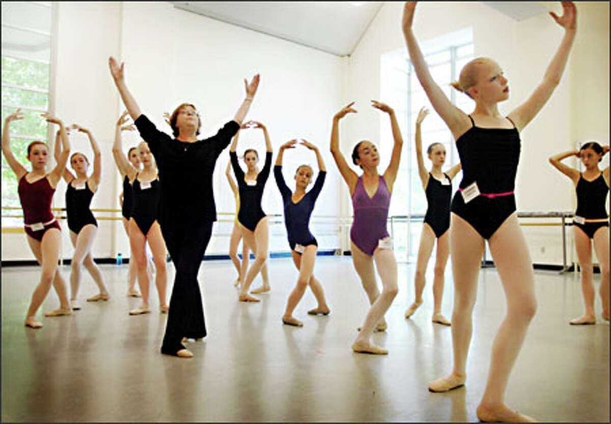 Pacific Northwest Ballet faculty member Victoria Pulkkinen works yesterday with young students, including Christina Blankenship, 12, from Minnesota, right foreground, during PNB's summer course and workshop program at its studios on Mercer Street.