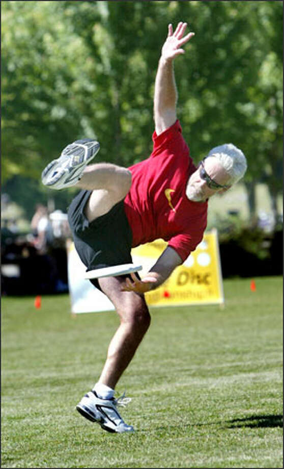 "Steve ""Boston Pops"" Scannell pirouettes as he snags the Frisbee during the pairs competition at the 2005 Freestyle Frisbee World Championships & Alternative Sports Festival at Green Lake. Scannell figures he is the oldest competitor at 57, hence the nickname. Photo: Scott Eklund, Seattle Post-Intelligencer / Seattle Post-Intelligencer"