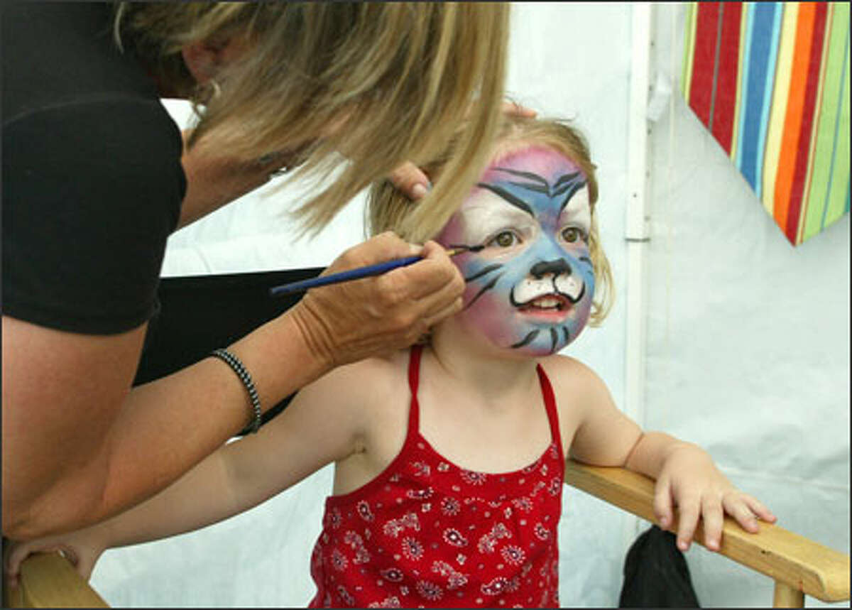 Jane Egnor, 3, gets a rainbow tiger painted on her face at the Capitol Hill Block Party in Seattle.