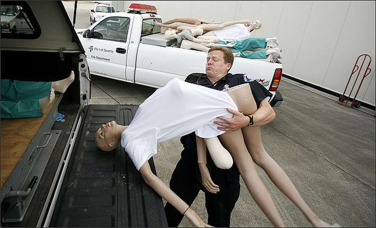 Seattle Fire Department Lt. Ben Haskell struggles to keep a mannequin intact while loading to transport it to the scene of a simulated airplane crash for a preparedness drill at Seattle-Tacoma International Airport.