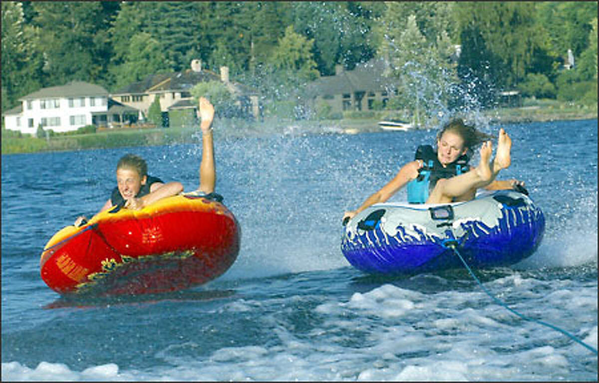 Dallin Nead, 14, of Maple Valley and his sister, Kaylene, 16, try to hang on while tubing on Lake Sammamish.