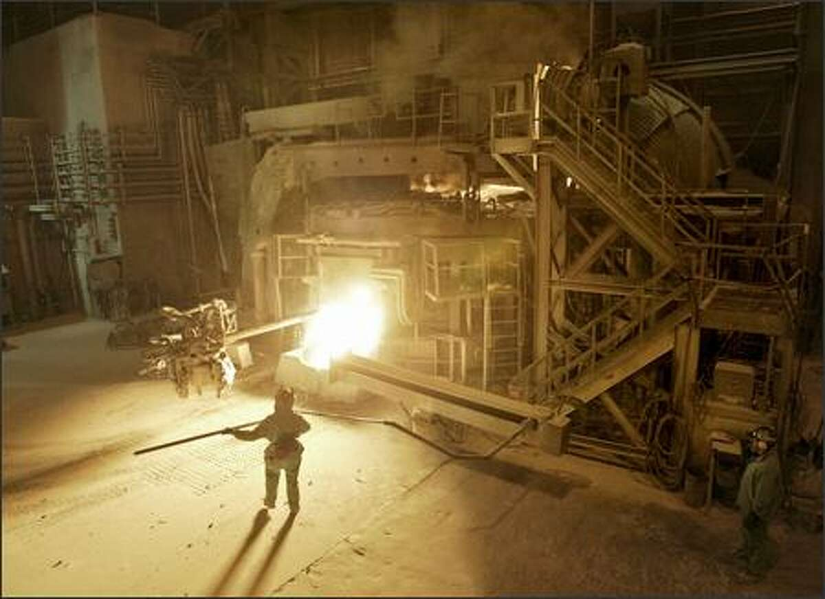 Nucor Steel Seattle, Inc. worker Cedric Johnson prepares to use a probe to check the temperature of the molten steel in an electric arc furnace. The West Seattle steel plant is celebrating its 100th anniversary.