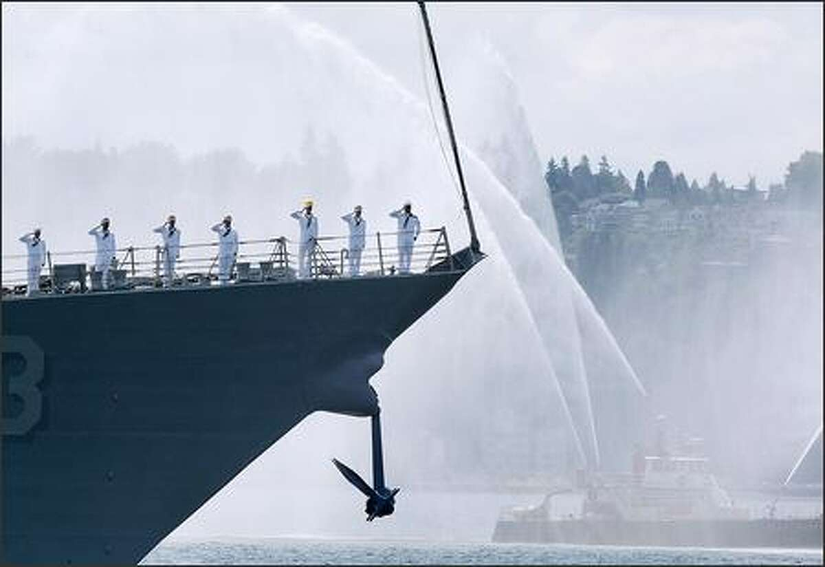 As a Seattle fireboat sprays water, sailors aboard the USS Chung-Hoon salute as they pass Pier 66 in downtown Seattle during the U.S. Navy Fleet Parade of Ships in Elliott Bay on Wednesday, part of the festivities preceding Seafair's climactic weekend.