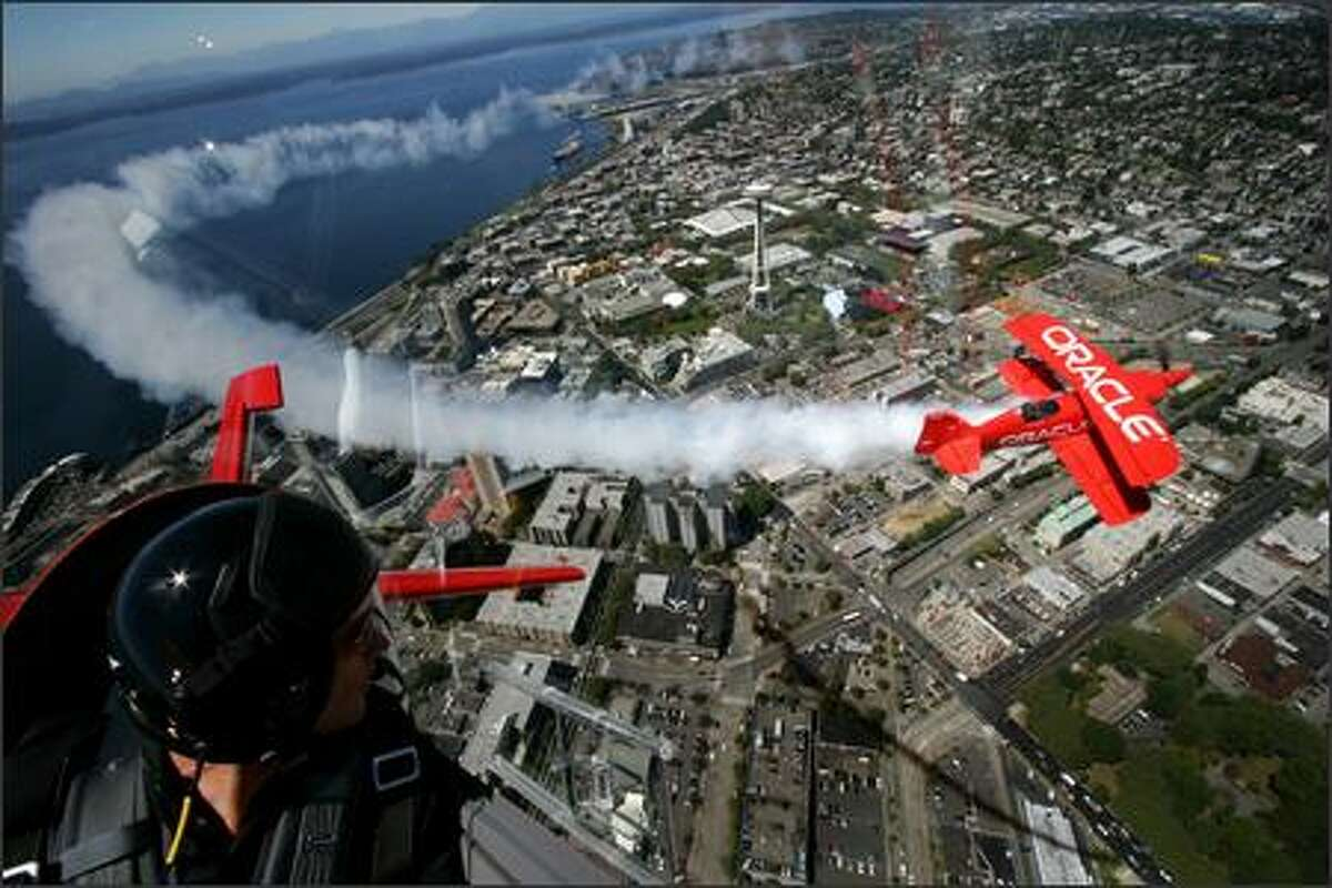 Team Oracle pilot Eric Tucker, left, watches as his father, reknown aerobatic pilot Sean Tucker fly in formation as they practice over Seattle on Thursday August 2, 2007. The planes are in town and are practicing and preparing their show for Seafair.