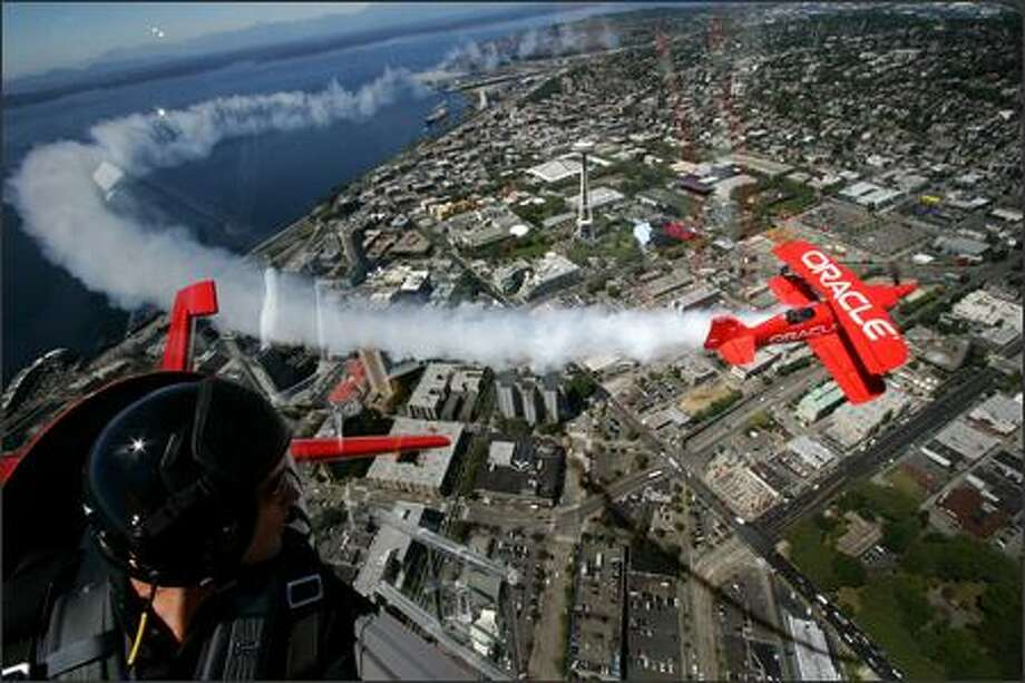 Team Oracle pilot Eric Tucker, left, watches as his father, reknown aerobatic pilot Sean Tucker fly in formation as they practice over Seattle on Thursday August 2, 2007. The planes are in town and are practicing and preparing their show for Seafair. Photo: Joshua Trujillo, Seattlepi.com / seattlepi.com