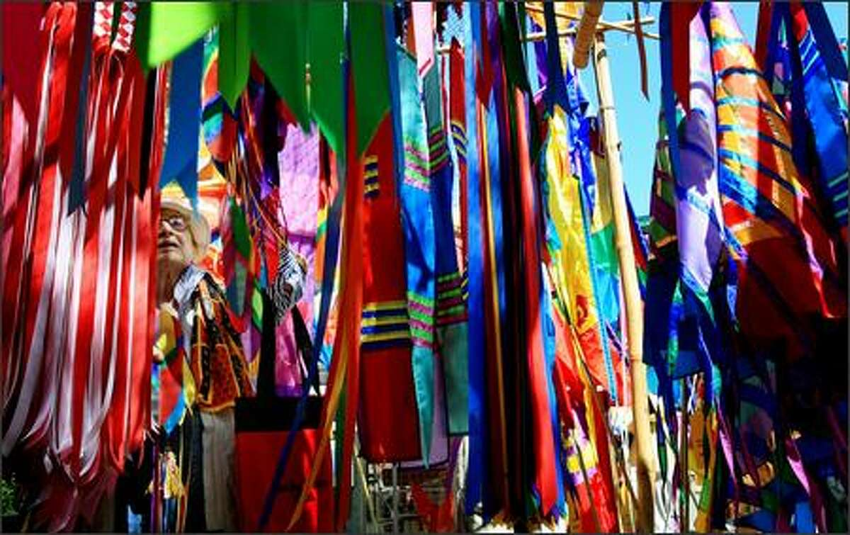 Jan Kozicki of Juanita, WA shops for banners at the colorful display of SoundWinds/AirArts, a Seattle company, at Bellevue Arts Museum ArtsFair on Friday, July 27, 2007.