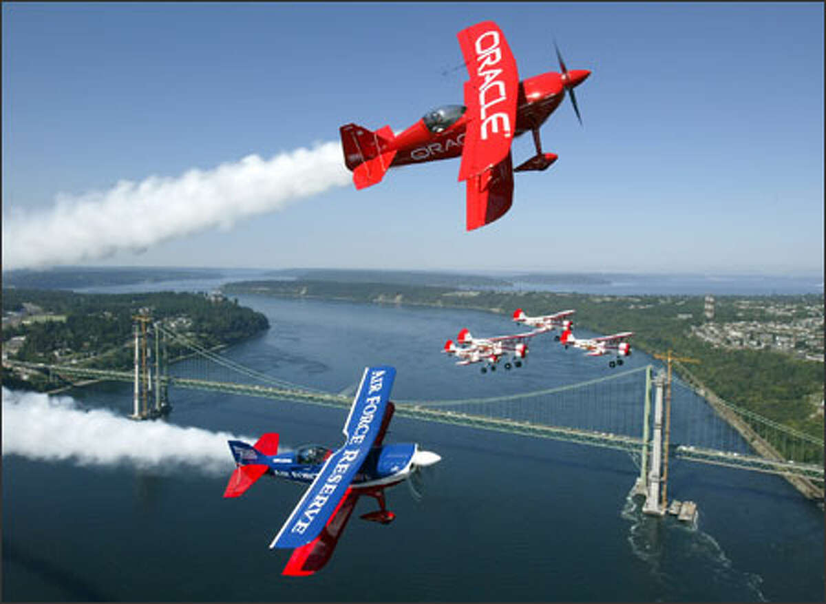 Sean Tucker with Team Oracle, Ed Hamill with the Air Force Reserve Aerobatics Show and the Red Baron Squadron fly over the Tacoma Narrows Bridge.