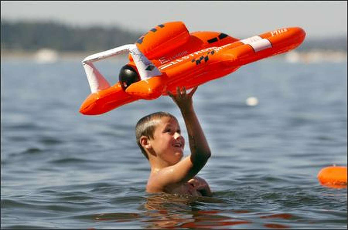 Tim Allen, 8, from Mossyrock, plays with his inflatable hydroplane in Lake Washington.