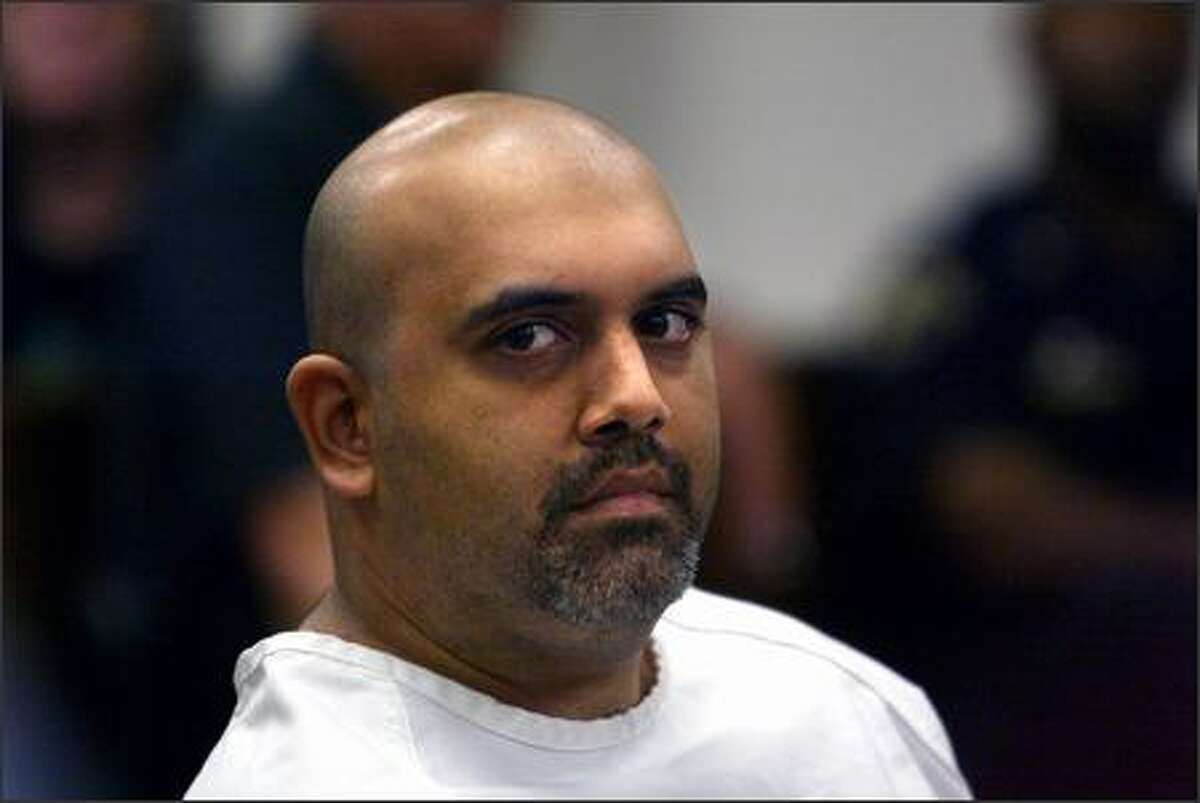 Naveed Haq, accused of shooting six women and killing one at the offices of the Jewish Federation of Greater seattle, stares at the media during a court hearing on Tuesday. On Thursday, Haq tried to plead guilty at his arraignment but legal experts say it's uncertain whether he will be allowed to do so while questions remain about his mental state and the prosecutor has not yet decided whether to seek the death penalty.