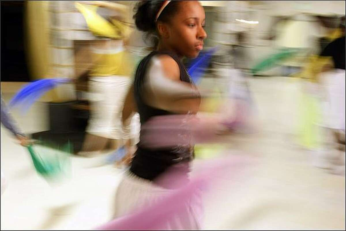 """Taylor Fuller, 14, participates in a scene called """"Beautiful Africa"""" during a rehearsal for """"Snow White & The 7"""" at the Langston Hughes Performing Arts Center. The play is the 12th annual all city youth summer musical."""