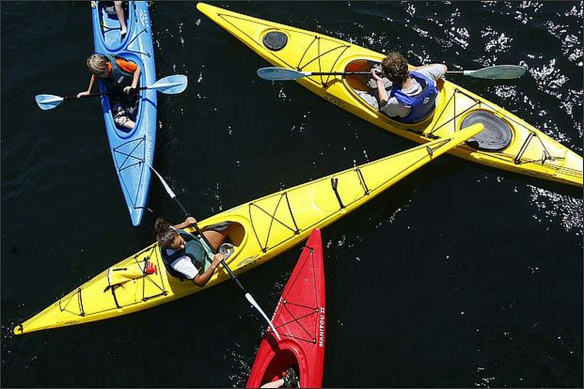 A group of kids and instructors from the Moss Bay Kids Camp converge beneath the South Lake Union Park footbridge while playing a game in their kayaks.