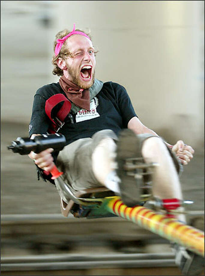 With just enough strength left to keep hold of the beer in his water bottle, Herman Beans rides a pedal-powered centrifuge during the party after the weekend's Eighth Annual Downhill and Messenger Challenge. Photo: Mike Urban, Seattle Post-Intelligencer / Seattle Post-Intelligencer