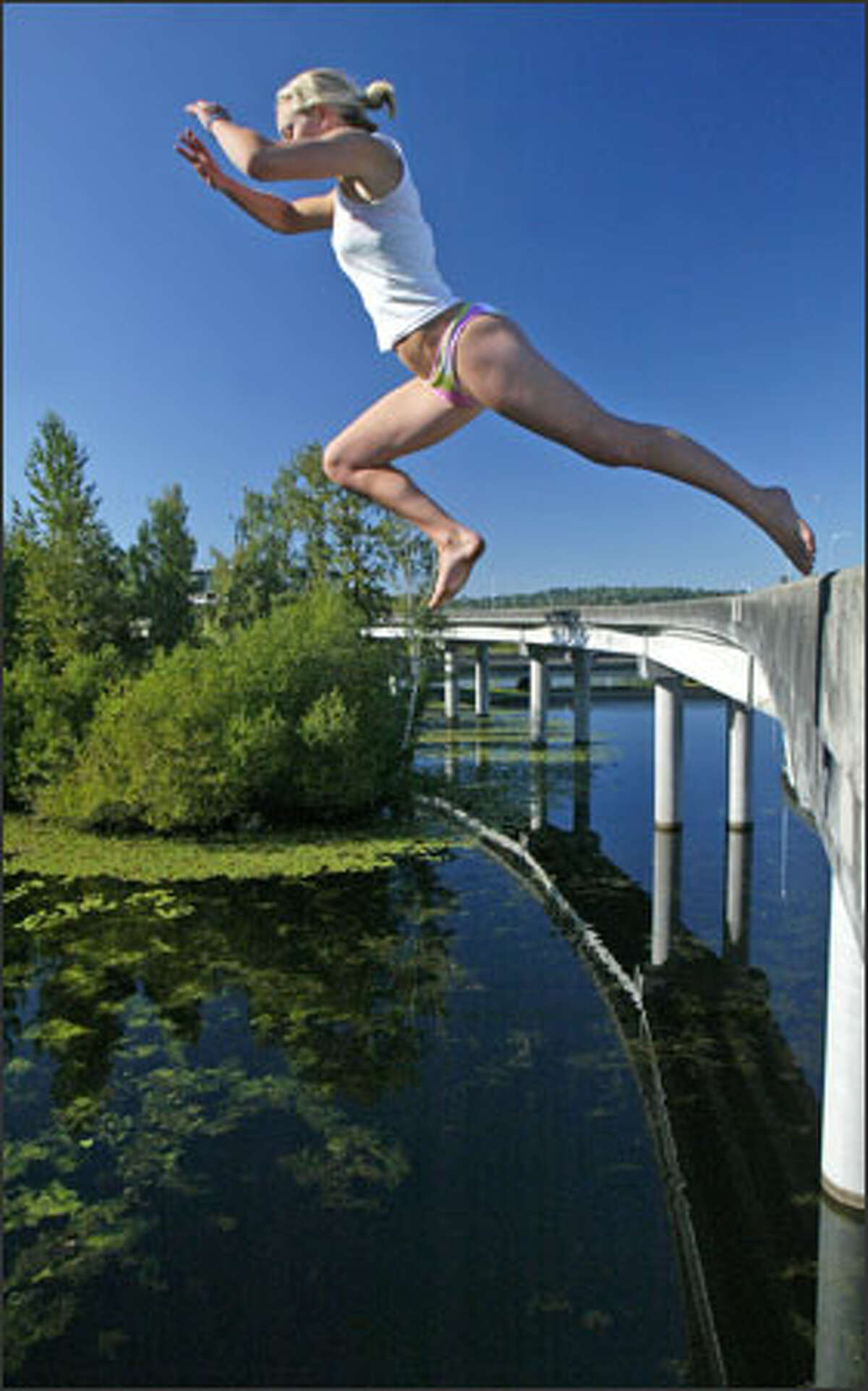 Alex Merrick takes a flying leap off a closed and unused section of the state Route 520 Bridge into the cool water of the Washington Park Arboretum below. The bridge is a perennially popular spot for people seeking relief from the heat after summer officially arrives.