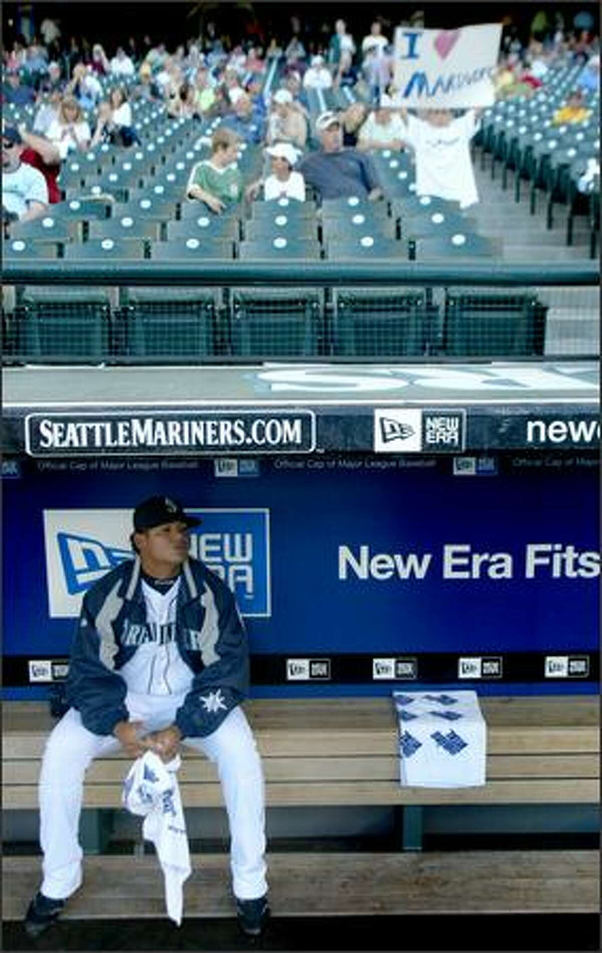 New Mariners pitcher Felix Hernandez sits alone in the dugout before his first start at Safeco Field. He allowed just five hits and no walks in eight innings to win 1-0.