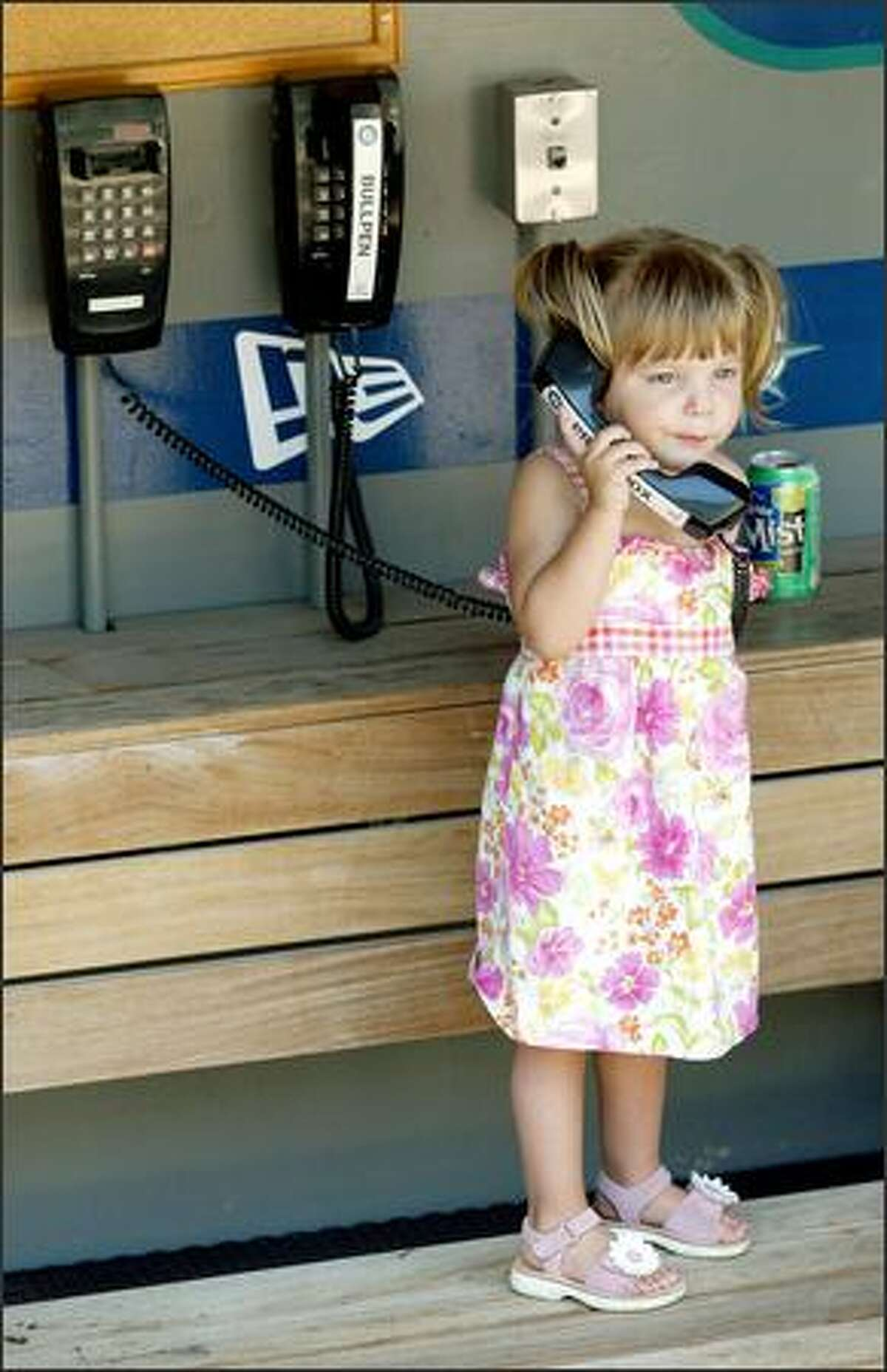 Tessa Martinez plays with the phone in the visitor's dugout at Safeco Field following her father's announcement.