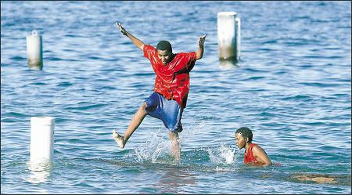 Misker Malle, 15, left, and his brother, Yinebeb Malle, 10, of Seattle, take turns jumping off a log at Pritchard Beach in Seattle. Highs were in the low 90s in the Puget Sound region yesterday, although no records were broken.