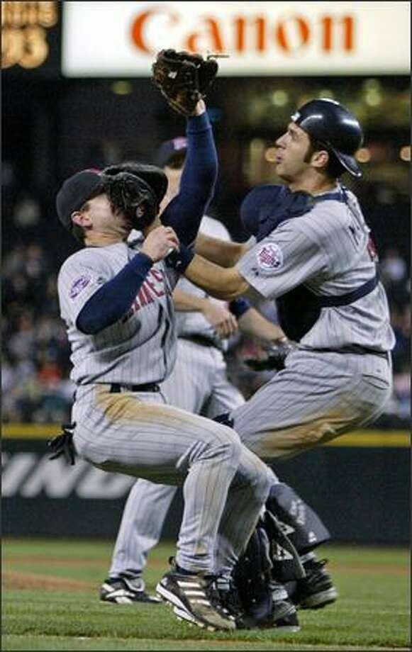 Minnesota Twins catcher Joe Mauer whacks third baseman Nick Punto as they try unsuccessfully to catch Ichiro Suzuki's bunt in the 12th inning of Wednesday's game. The Twins won 7-3 after 14 innings. Photo: Joshua Trujillo, Seattlepi.com / seattlepi.com