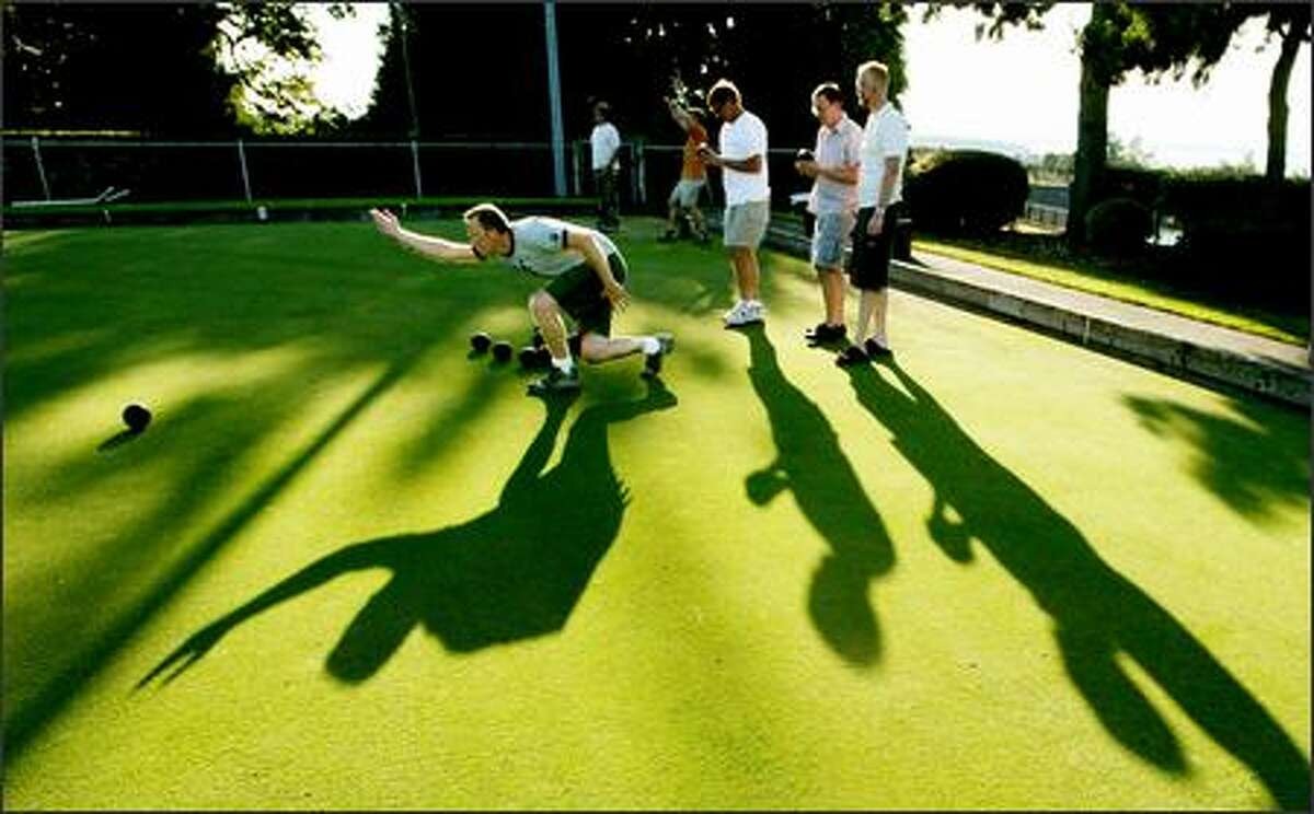 Pete Smith lets loose with a practice bowl prior to the start of the Tuesday night lawn bowling league Aug. 2 as (left to right) Ken Leu, Ryan Leu and Anthony Peiffer look on.