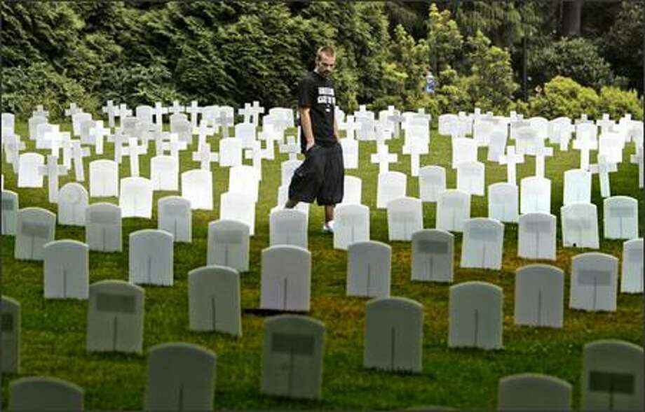 Army veteran Steve Mortillo searches for fallen friends among grave markers on display outside of the HUB at the University of Washington on Thursday. Mortillo, of New Jersey, served in Iraq in 2004-05. He is now a member of Iraq Veterans Against the War and was participating in a Veterans for Peace convention. Mortillo said the names of 12 of his friends who were killed in Iraq were on the markers. Photo: Gilbert W. Arias, Seattle Post-Intelligencer / Seattle Post-Intelligencer