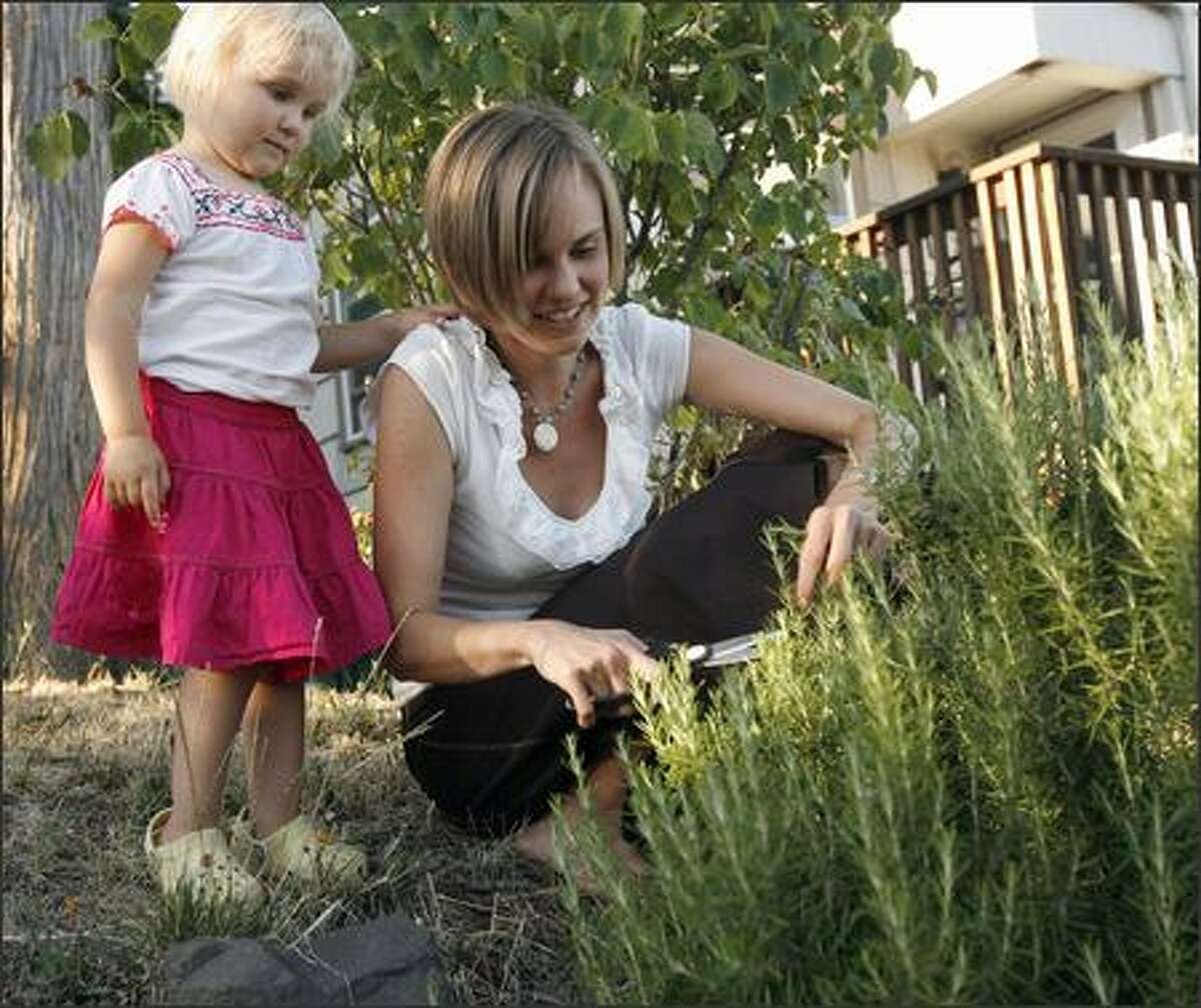 Melissa and her daughter Chloe, 2, cut rosemary in their front yard. Melissa is following the