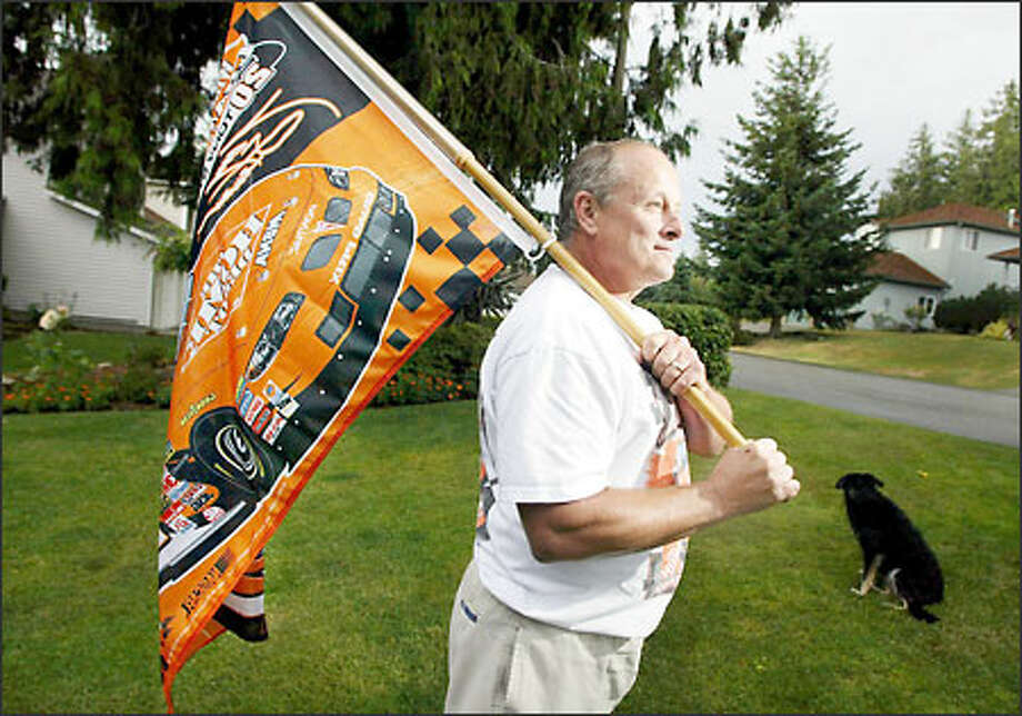 NASCAR devotee Mike Benedict displays this flag, which signifies 2002 champion Tony Stewart, in his front yard in the Gleneagle neighborhood in Arlington. Photo: Meryl Schenker, Seattle Post-Intelligencer / Seattle Post-Intelligencer