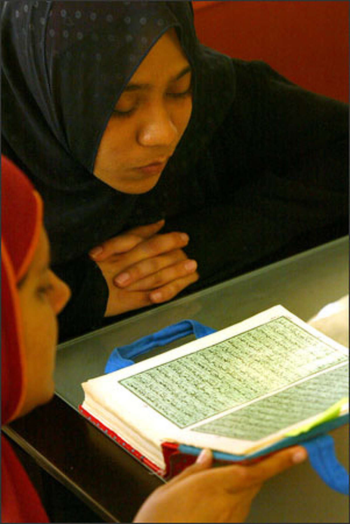 Zakiya Qadir, right, takes Quran lessons at her mosque at Northgate recently. Qadir, a University of Washington student, says for Muslims, high school is