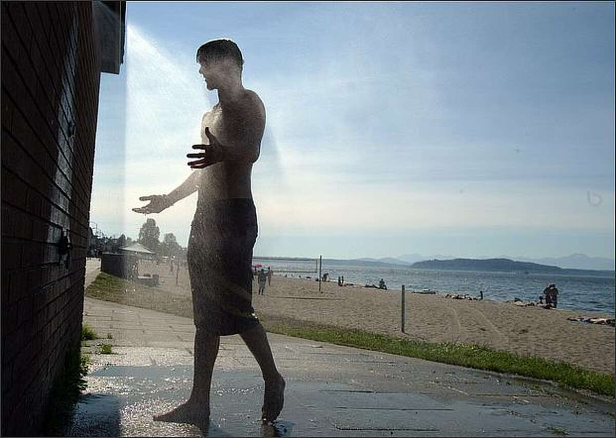 Ian Keithly, 17, showers off the salt water at Alki Beach. Temperatures are expected to reach 90 degrees today.