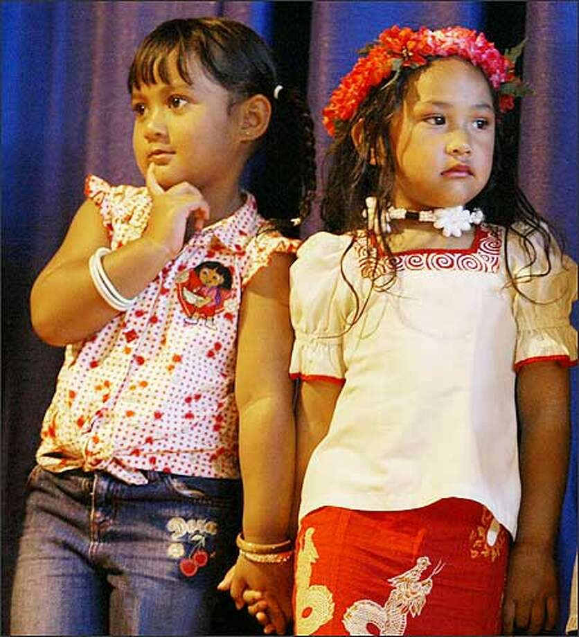 "Letavia Laga, 5, left, and Merina Sanchez, 4, stand on stage at the Pasefika School Readiness program's ""End of Program Celebration"" at Cascade Middle School, where the children showed what they learned this summer. Photo: Meryl Schenker, Seattle Post-Intelligencer / Seattle Post-Intelligencer"