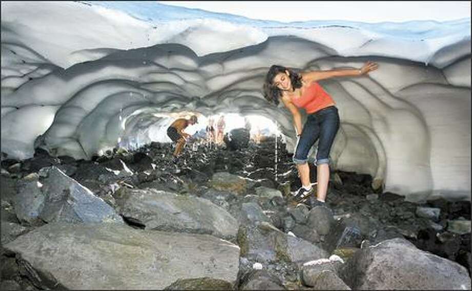 Ingred Resch, 16, of Germany, cools off as she explores the inside of a small ice tunnel with family and friends yesterday near the Table Mountain and Chain Lakes trailhead in the Mount Baker Wilderness. Larger ice caves can be dangerous, and park authorities warn against entering them because of possible collapse. Ice caves are formed as snowfields melt, often with water carving out the tunnel as it flows underneath. Photo: Joshua Trujillo, Seattlepi.com / seattlepi.com