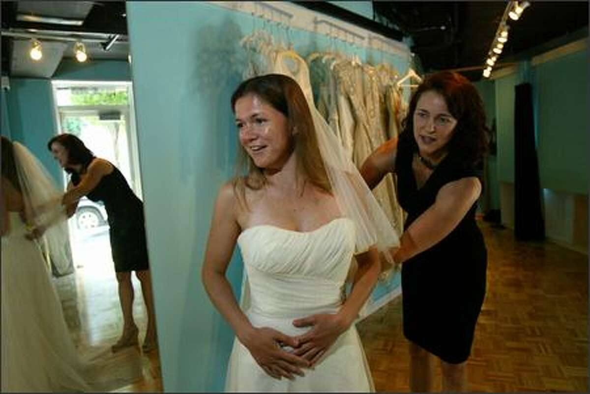 Erica Stillner tries on wedding dresses at the Belltown Bride, a couture bridal outlet owned by Melissa Albert (right) which sells wedding dresses for at least 50% off but come in limited sizes.