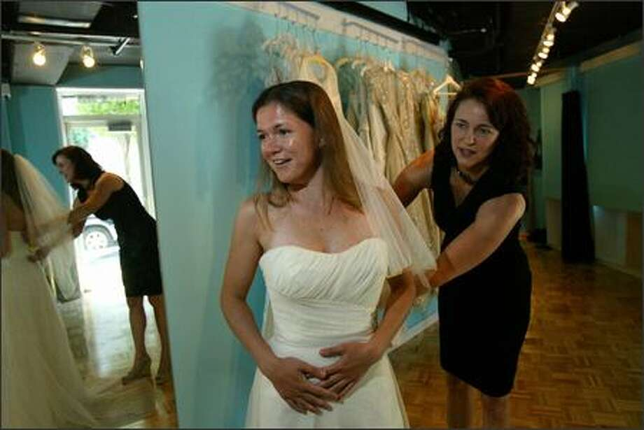Erica Stillner tries on wedding dresses at the Belltown Bride, a couture bridal outlet owned by Melissa Albert (right) which sells wedding dresses for at least 50% off but come in limited sizes. Photo: Karen Ducey, Seattle Post-Intelligencer / Seattle Post-Intelligencer