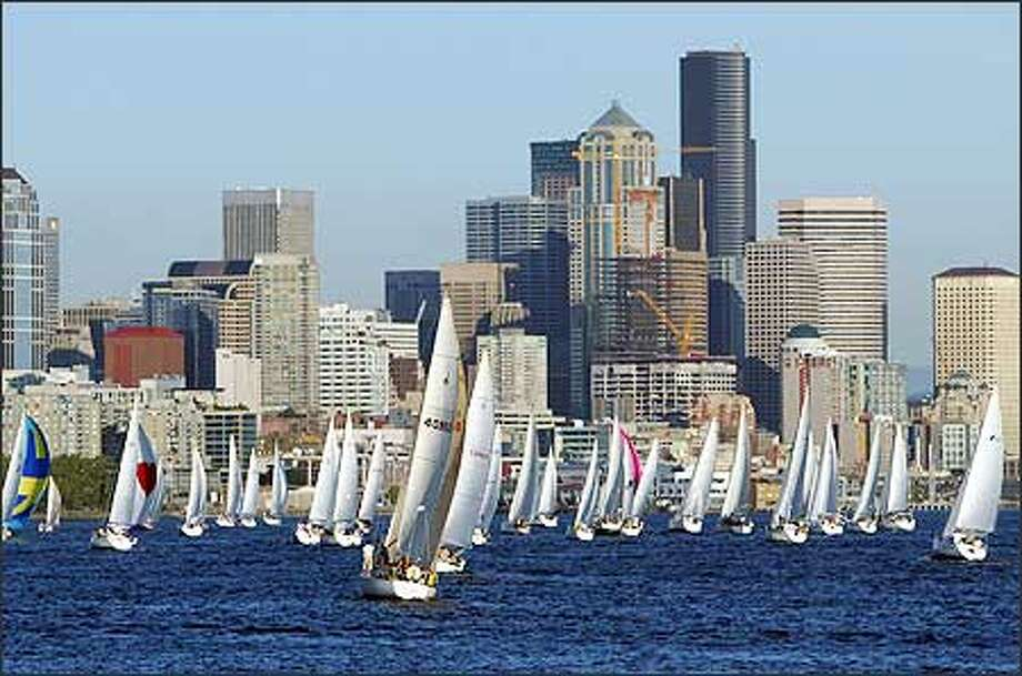 More than 70 sailboats head toward Seattle's high-rises before making the first turn Thursday evening in the 12th and final round of this summer's Downtown Sailing Series on Elliott Bay. Photo: Grant M. Haller, Seattle Post-Intelligencer / Seattle Post-Intelligencer