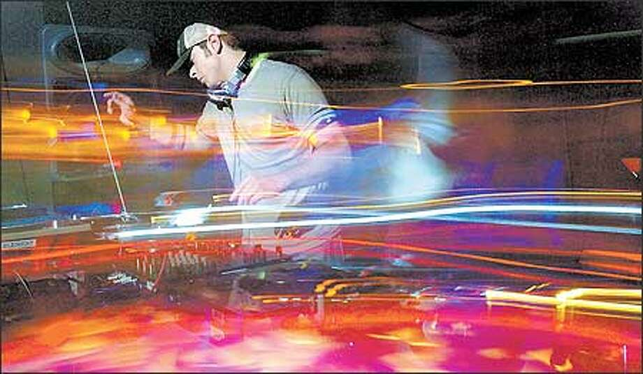 A swirl of sound -- represented by special camera effects -- wraps DJ Joshua James during the Spin-Off contest at Seattle's Element club. James, a finalist, lets the crowd's energy inspire his playlist. Photo: Grant M. Haller, Seattle Post-Intelligencer / Seattle Post-Intelligencer