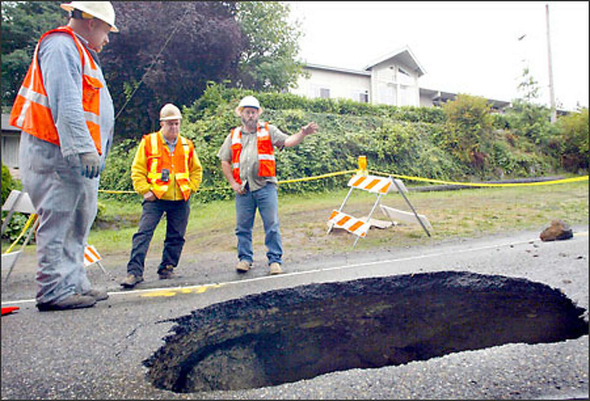Garrick Hopkins, left, Dick Gabrielson and Bob Lucas of Seattle Public Utilities discuss ways to fill a sinkhole on Orcas Street near 30th Avenue South in Seattle. A pipe burst yesterday, eroding the ground under the street.