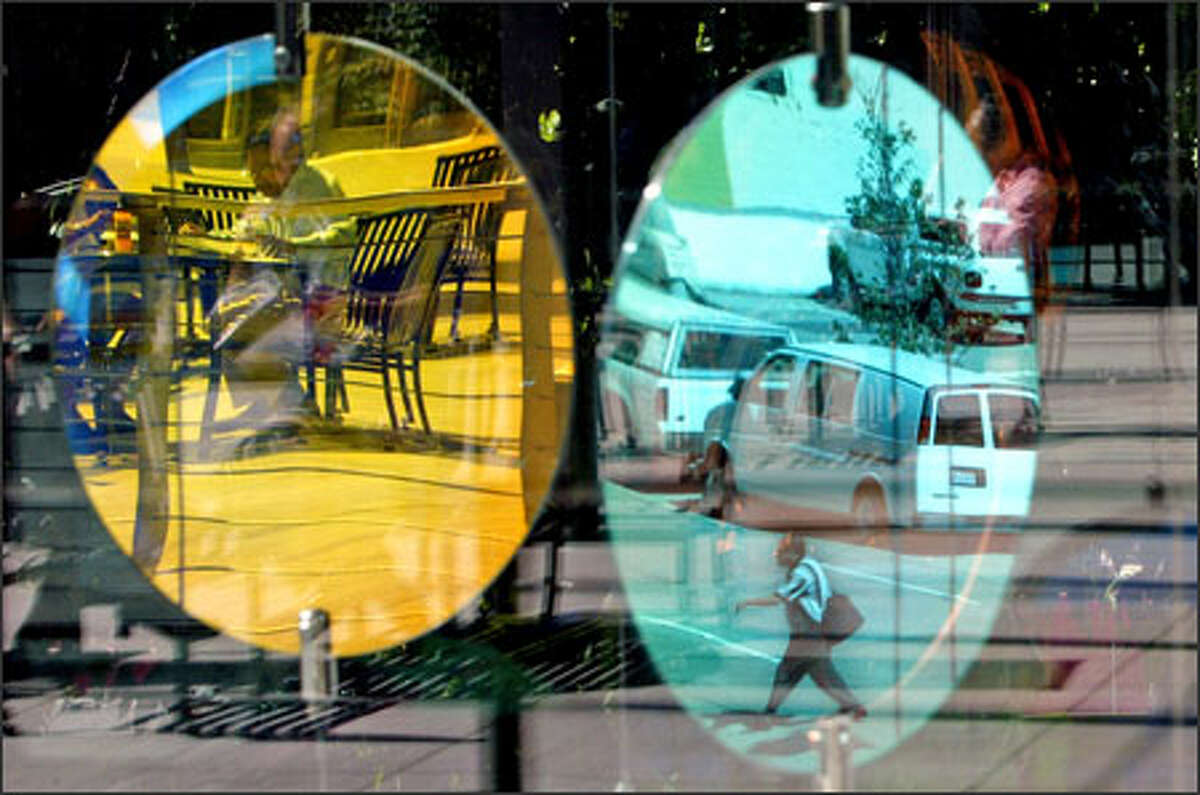 """City images are reflected in an art installation at City Hall during a warm lunchtime. Artist Beliz Brother says the piece, titled """"illume,"""" creates an """"abstraction of color and light"""" by using """"reflection of the surrounding environment."""""""