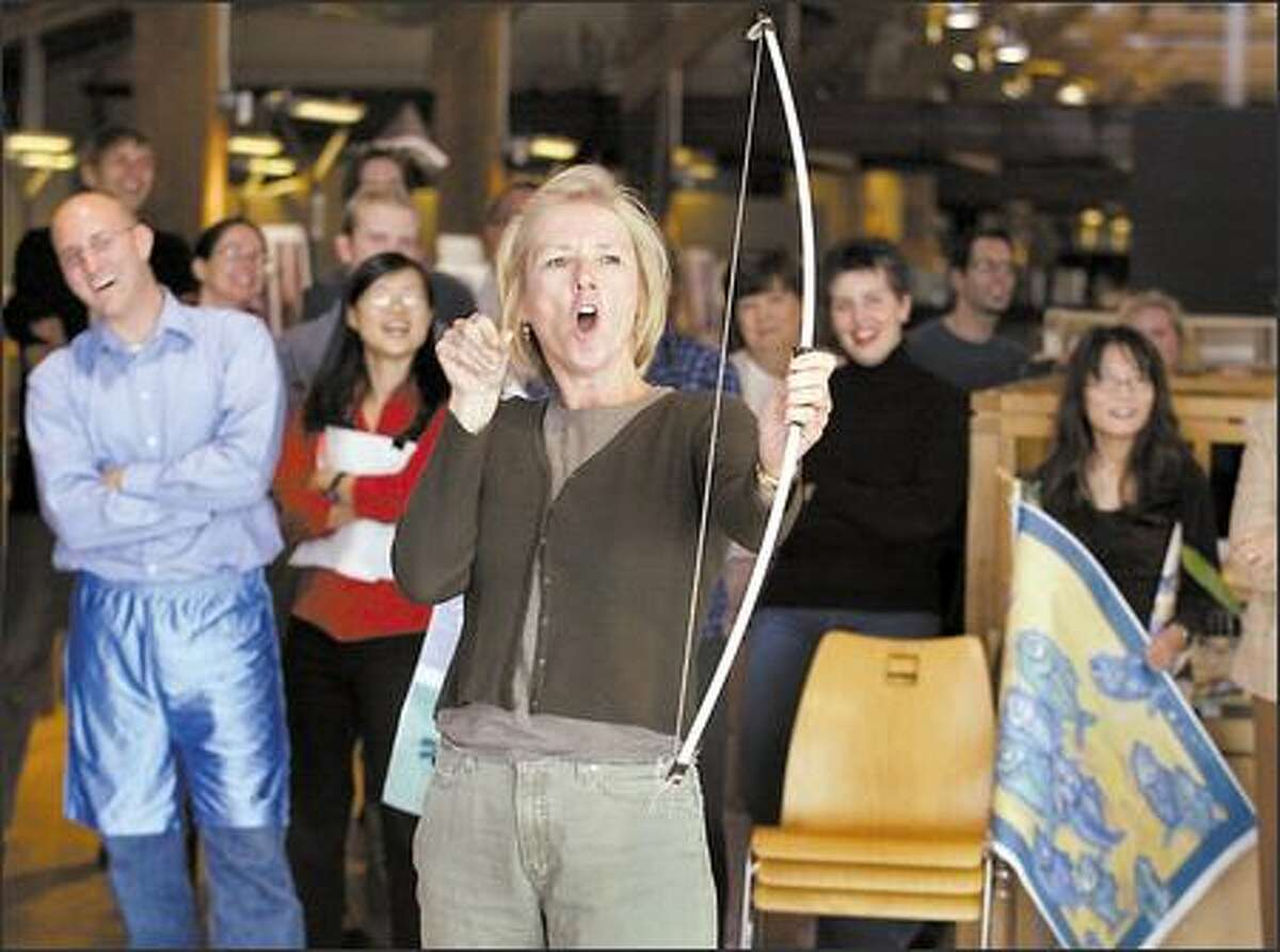 Lisa Folkins, a site planner and principal at Seattle architecture firm Mithun, reacts to her shot with a toy bow at the company's second Mithun Olympics, held in honor of the international sporting event. Company employees took a break during the workday to participate in an archery competition.