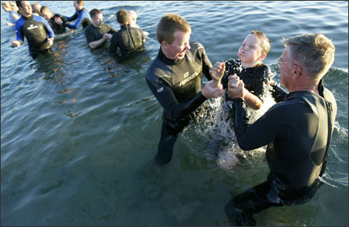 Mars Hill pastor Steve Tompkins, left, with the help of pastor Bent Meyer, baptizes his son Sam Tompkins, 9, in the chilly water at Golden Gardens Park.