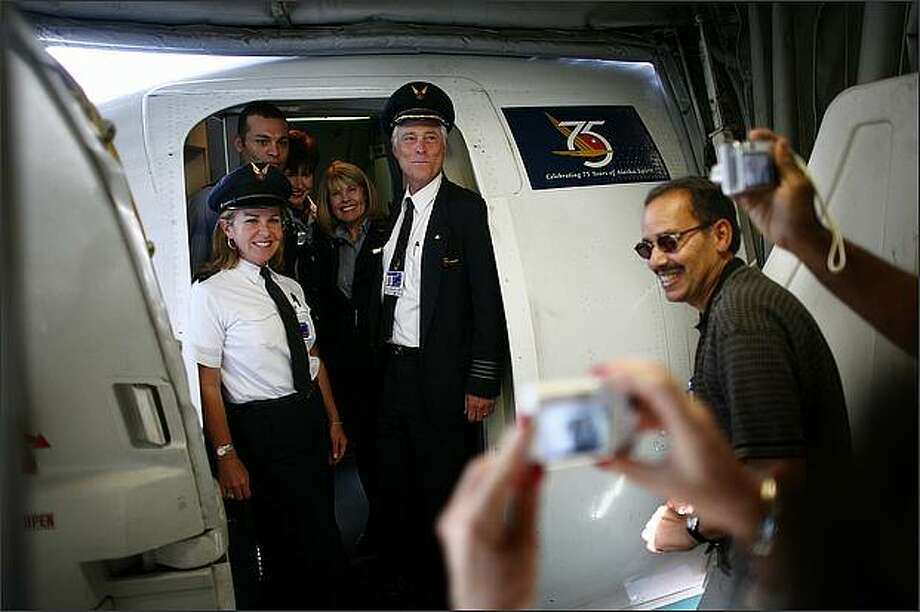 Guests take pictures of Claude Tirman, his daughter Dana Haines, left, and the flight crew on Tirman's final flight as an Alaska Airlines pilot. Tirman retired from the airline after 27 years with his final flight from California to SeaTac. Photo: Joshua Trujillo, Seattlepi.com / seattlepi.com