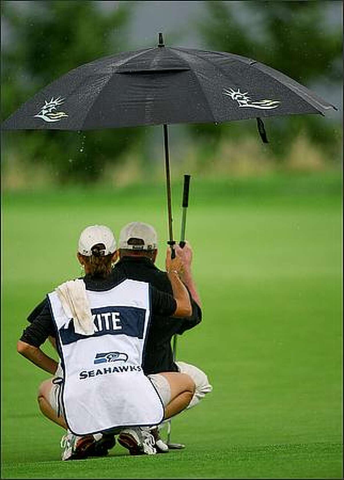 Tom Kite's caddie keeps him dry as they eyeball the putt on the 13th hole during the final round of the 2008 Boeing Classic on the Champions Tour at the TPC at Snoqualmie Ridge.