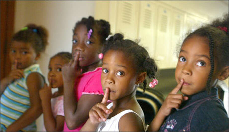 "From left, kindergartners Dalilah Hampton, Zakiya Shabazz, Tajzhanee Blue, Kamaia Bland and Shania Lowery keep their fingers over their lips to remind themselves that the hall is a quiet place. All five youngsters were attending the ""Kindergarten Academy"" at Seattle's Martin Luther King Elementary. Photo: Karen Ducey, Seattle Post-Intelligencer / Seattle Post-Intelligencer"