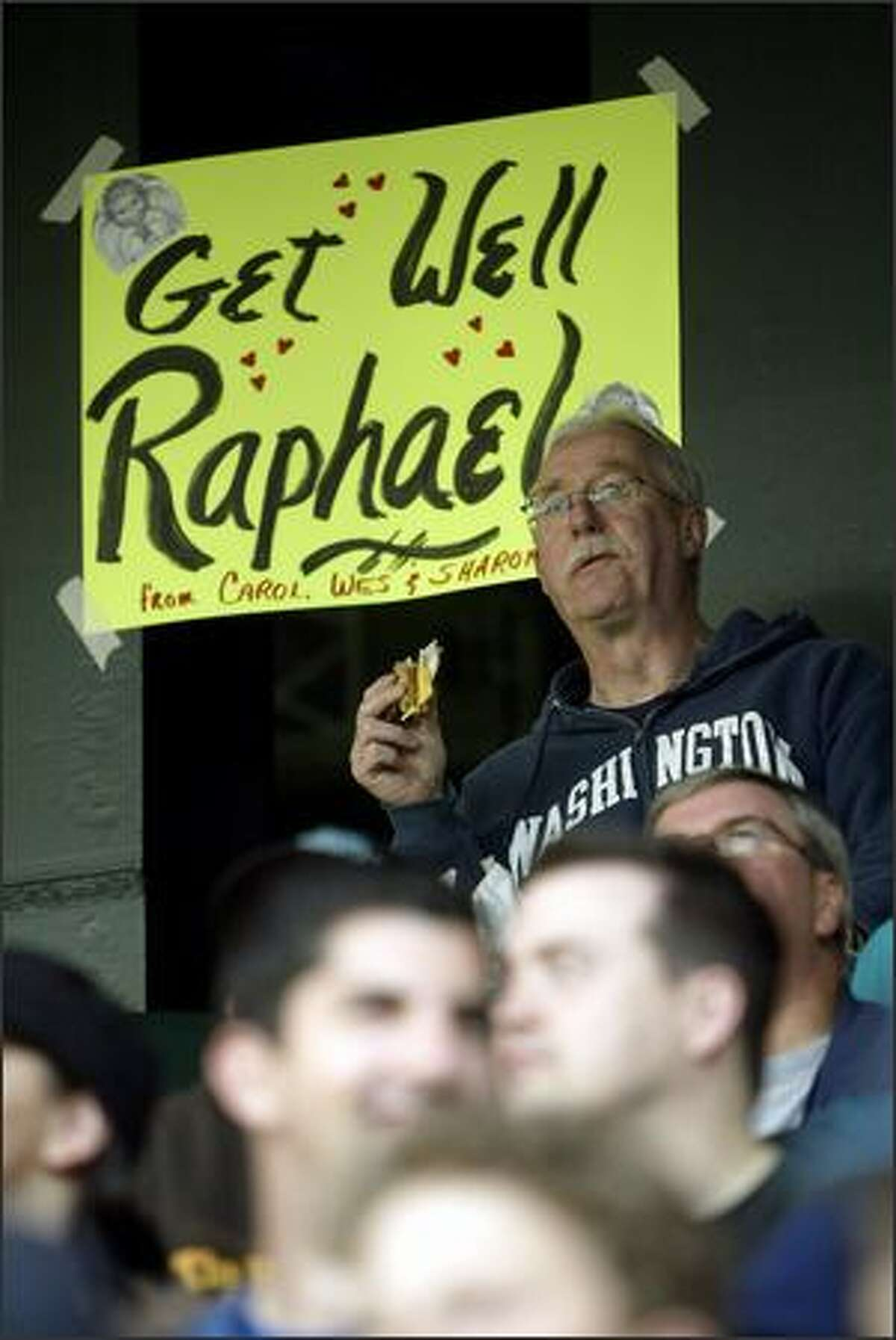 Mariners fan Rich Kemp, of Seattle, watches the game from the 200 level in front of a sign in support of injured player Rafael Soriano posted by other fans.
