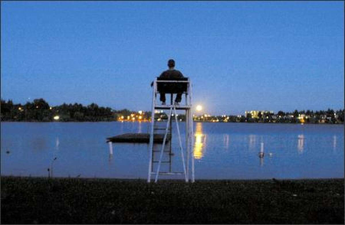 With August over and most of another summer behind him, Richard Clairmont takes time to meditate while sitting on a lifeguard's chair at Green Lake as the moon rises above the skyline.