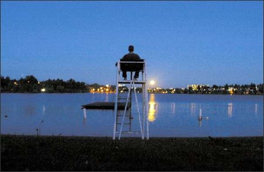 With August over and most of another summer behind him, Richard Clairmont takes time to meditate while sitting on a lifeguard's chair at Green Lake as the moon rises above the skyline. Photo: Grant M. Haller, Seattle Post-Intelligencer / Seattle Post-Intelligencer